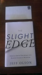 """Image of book titled """"The Slight Edge"""" by Jeff Olson, with an unaddressed but stamped envelope placed above it"""